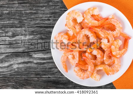 boiled tails of king shrimps on a white dish, on a table mat, on an old rustic blank space left, view from above