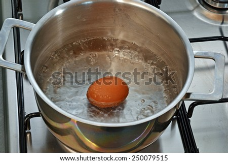 Boiling egg on metallic pan.
