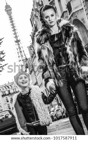Boiling hot trendy winter in Paris. modern mother and daughter nearby Eiffel tower in Paris, France walking