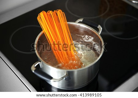 Boiling pasta in pan on electric stove in the kitchen - stock photo