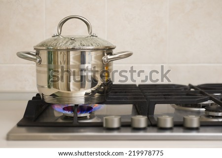 Boiling pot on the gas stove fire - stock photo