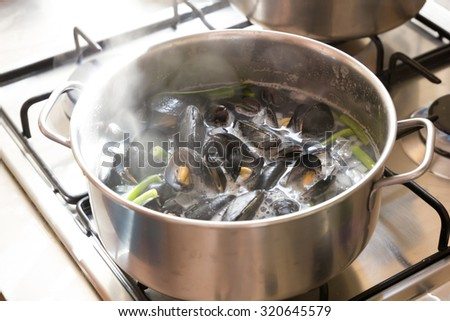 Boiling sea mussels in wine in a pot - stock photo
