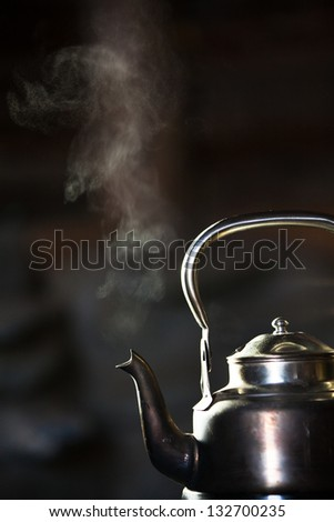 Boiling silver kettle on a wood stove - stock photo