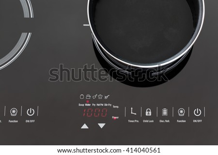 Boiling water at pan on Induction stove top panel, closeup - stock photo