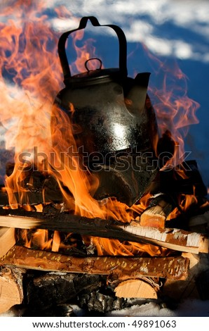 Boiling water in a kettle over an open fire in the winter snow, for a nice cup of coffee - stock photo