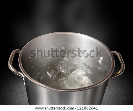 Boiling water in a kitchen pot as a symbol of cooking or food preparation and sterilization of contaminated tap water for healthy pure drinking liquid on a black background. - stock photo
