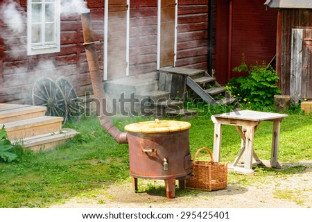 Boiling water in large stove for outdoor laundry. Smoke come out of chimney. Red wooden house in background. This is how it was done in the old times.