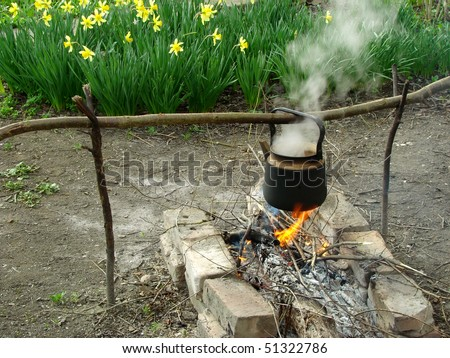 boiling water in old sooty kettle on the hiking campfire - stock photo