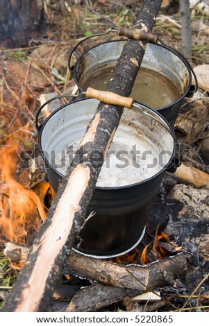 Boiling water in pails above the fire in camping