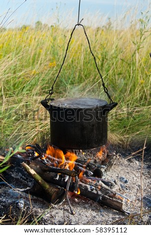Boiling water in pots above the fire