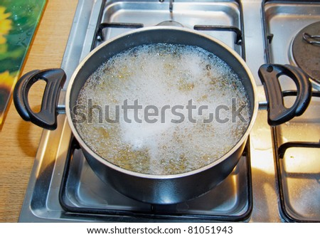 Boiling water inside a kitchen iron pot - stock photo