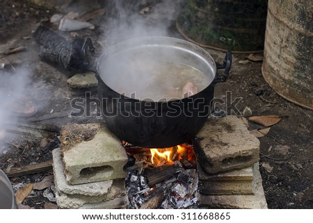 Boiling water  pots above the fire.