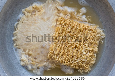 Boiling water with noodles in the steel pan - stock photo