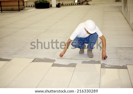 Boise, ID Aug 15, 2008 A tile worker measuring for placement on the new ceramic tile floor in a commercial retail mall.  He is depicted observing all safe workplace practices.