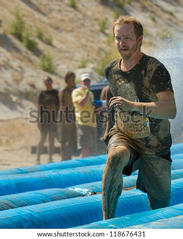 BOISE, IDAHO - AUGUST 25: Runner 14638 going fast on the slide at the Dirty Dash August 25 2012 in Boise, Idaho - stock photo