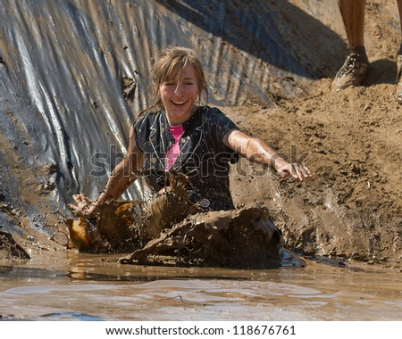 BOISE, IDAHO - AUGUST 25: Unidentified woman makes a splash at the bottom of the slide during the Dirty Dash August 25 2012 in Boise, Idaho - stock photo