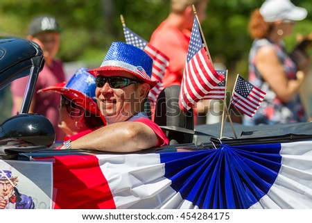 BOISE, IDAHO - JULY 4, 2016: Man in his car that is filled with american flags during the 4th of July Parade in Boise, Idaho