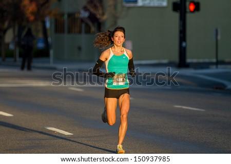 BOISE, IDAHO - NOVEMBER 22: Runner 928 runs to the finish line during the Turkey Day 5k in Boise, Idaho on November 22, 2012 - stock photo