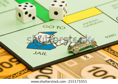 BOISE, IDAHO - NOVEMBER 18, 2012:  The car piece is speeding away from the go to jail spot on the famous Hasbro game Monopoly. - stock photo