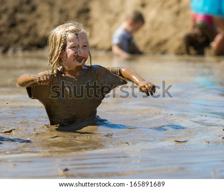 BOISE, IDAHO/USA - AUGUST 10: Child works their way through the pit of mud at the The Dirty Dash in Boise, Idaho on August 10, 2013 - stock photo