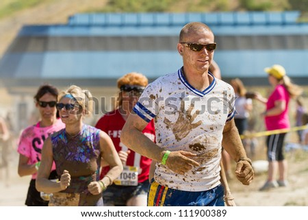 BOISE, IDAHO/USA - AUGUST 25:Crowd runs during the Dirty Dash covered in mud. The Dirty dash is a 10k run through obstacles and mud on August 25, 2012 in Boise, Idaho - stock photo