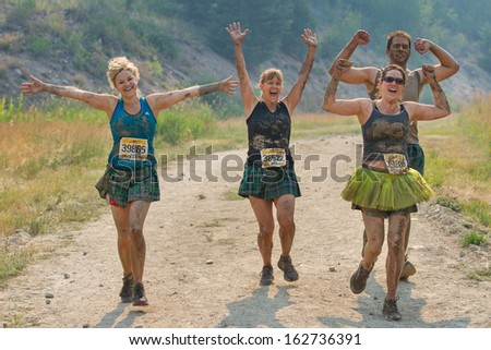 BOISE, IDAHO/USA - AUGUST 10: Group of runners having fun while running at the The Dirty Dash in Boise, Idaho on August 10, 2013  - stock photo