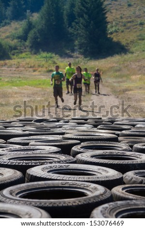 BOISE, IDAHO/USA - AUGUST 10: Group of runners race to the tire course at the The Dirty Dash in Boise, Idaho on August 10, 2013. Focus is shallow and set on the tires - stock photo