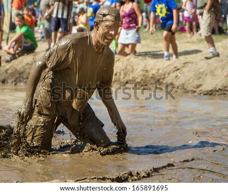 BOISE, IDAHO/USA - AUGUST 10: Man drips mud after standing up in the mud pit at the The Dirty Dash in Boise, Idaho on August 10, 2013 - stock photo