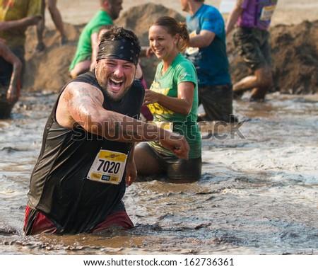 BOISE, IDAHO/USA - AUGUST 10: Runner 7020 runs through the mud at the The Dirty Dash in Boise, Idaho on August 10, 2013  - stock photo