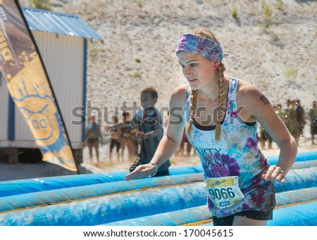 BOISE, IDAHO/USA - AUGUST 10, 2013: Runner 9066 trying to focus while working her way down the slide at the The Dirty Dash - stock photo