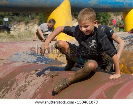 BOISE, IDAHO/USA - AUGUST 10: Unidentified child goes over an obstacle while he is covered in mud at the The Dirty Dash in Boise, Idaho on August 10, 2013  - stock photo