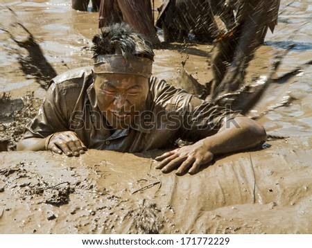 BOISE, IDAHO/USA - AUGUST 11, 2013:Unidentified man climbs up the last barrier at the dirty dash - stock photo