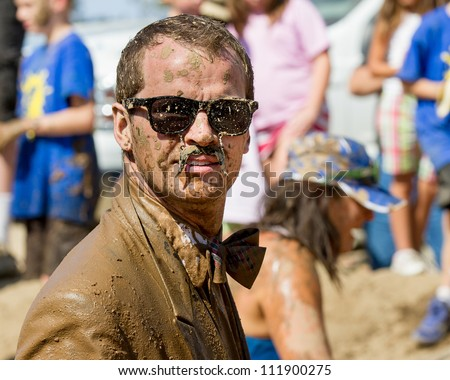 BOISE, IDAHO/USA - AUGUST 25: Unidentified man wearing mustache glasses and a suite during the dirty dash  The Dirty dash is a 10k run through obstacles and mud on August 25, 2012 in Boise, Idaho - stock photo