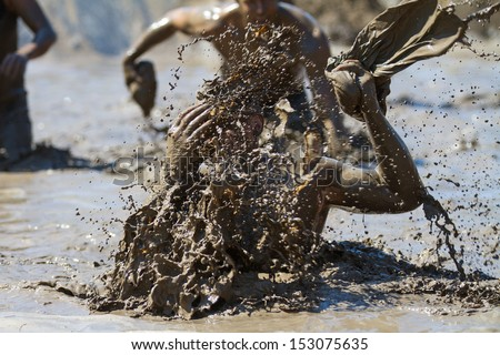 BOISE, IDAHO/USA - AUGUST 10: Unidentified person makes a huge splash in the mud. Event was held at the The Dirty Dash in Boise, Idaho on August 10, 2013  - stock photo