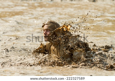 BOISE, IDAHO/USA - AUGUST 8, 2014: Unidentified swimmer is swimming through the mud pit near the finish at the Dirty Dash in Boise, Idaho - stock photo