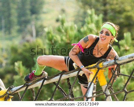 BOISE, IDAHO/USA - AUGUST 8, 2014: Unidentified woman passes the rope obstacle at the dirty dash  - stock photo
