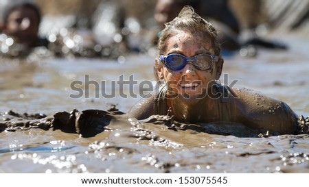 BOISE, IDAHO/USA - AUGUST 10: Unidentified woman pokes her head up from the mud while wearing goggles at the The Dirty Dash in Boise, Idaho on August 10, 2013  - stock photo