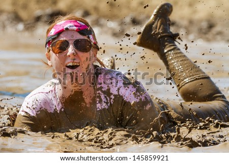 BOISE, IDAHO/USA - AUGUST 25 -  Woman playing in the mud at the dirty dash. The Dirty dash is a 10k run through obstacles and mud on August 25, 2012 in Boise, Idaho - stock photo