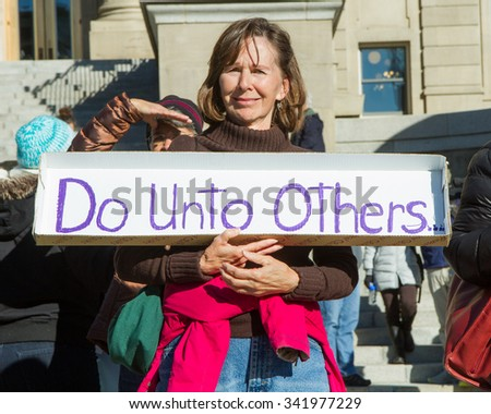 BOISE, IDAHO/USA - NOVEMBER 21, 2015: Woman sending her message with a sign regarding the Syrian refugees in Boise, Idaho - stock photo