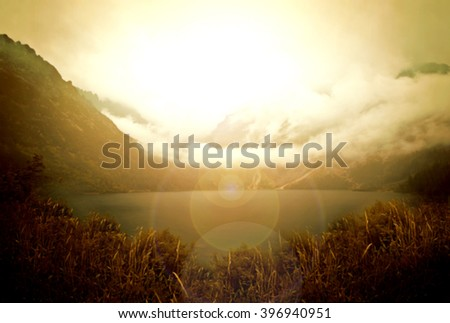 Bokeh abstract foggy mountains and lake landscape. - stock photo