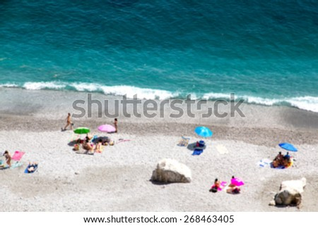 Bokeh effect of Ocean beach view with beautiful waves of clean transparent water and white sand, high altitude view of beautiful seashore with sunbathe people vacation and holiday concept, blur effect - stock photo