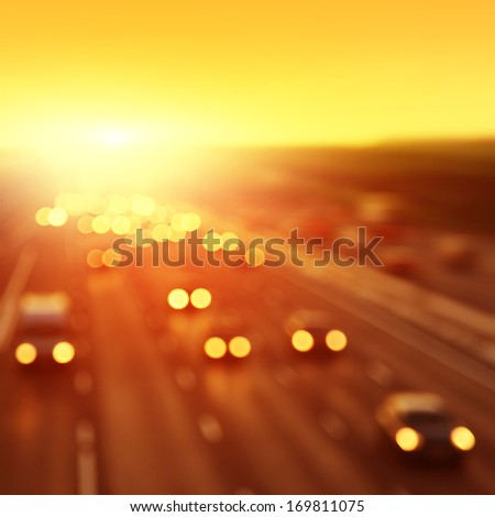 Bokeh lights of traffic during sunset. - stock photo