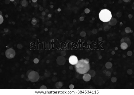 Bokeh lights on black background, shot of flying snowflakes in the air - stock photo