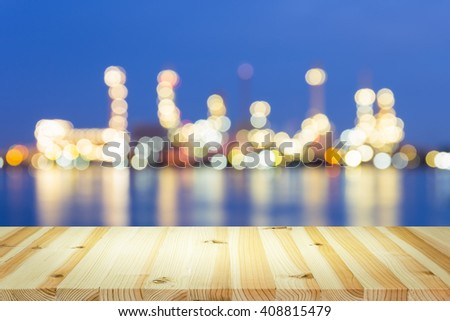 Bokeh of oil refinery at twilight with wood table. - stock photo