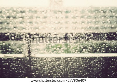 bokeh of raindrops on the glass with blur building background, vintage tone - stock photo