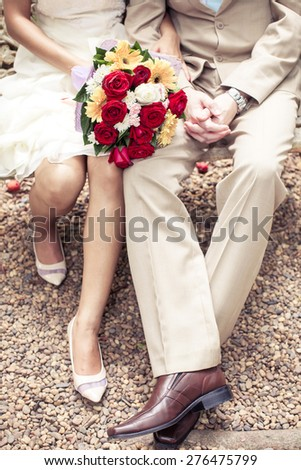 bokeh on hands of Bride and groom and sitting on the bench - stock photo