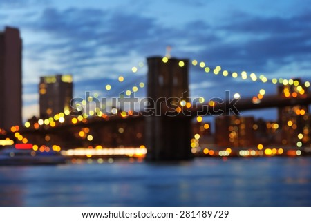 Bokeh photo of New York City Brooklyn Bridge with downtown skyline over East River at night  - stock photo