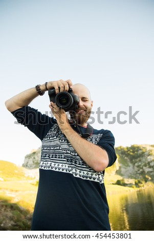 Bold man with a camera in a lake