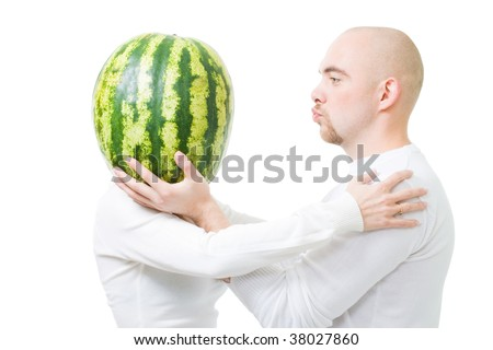 Bold young man kissing woman with head made of watermelon