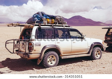 Bolivia, Altiplano-April, 2011: Tourist Expedition Altiplano plateau in the SUV. Off-road vehicles traveling on the road of the Andes. Stop the car in the desert of Bolivia for the rest.  - stock photo
